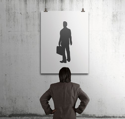 businessman looking at people icon on art frame on the wall as h