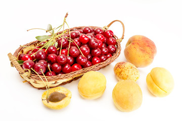 red cherries in a basket and ripe apricots
