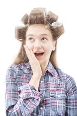 Surprised young girl in curlers