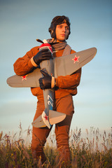 Guy in vintage clothes pilot with an airplane model outdoors