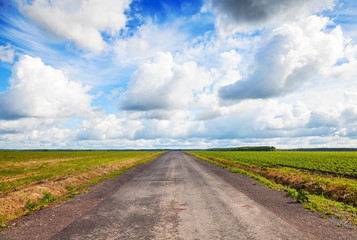 Empty country road perspective with dramatic cloudy sky