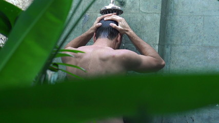 Young man taking shower outdoors, super slow motion