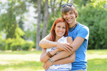 Teenage couple hugging in sunny park smiling