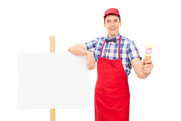 Ice cream seller standing by a blank signboard