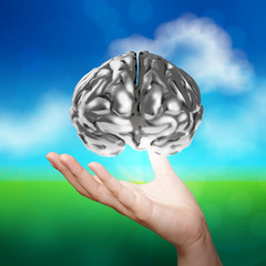 businessman hand showing 3d metal human brain on nature backgrou