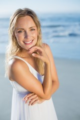 Pretty blonde standing at the beach in white sundress smiling at