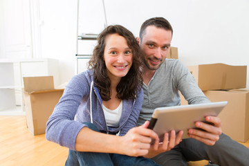 View of a Young couple using tablet while moving in new flat