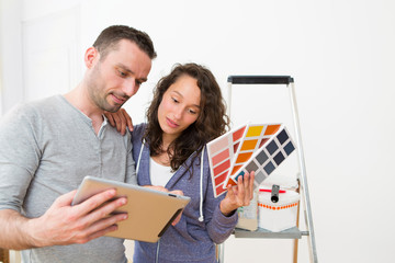Young couple choosing colors of their new flat