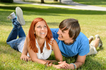 Teenage couple lying on grass laughing together