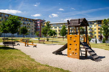 Children playground in nature in front of block of flats