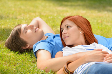 Romantic teenage couple lying on grass summer