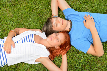 Young couple lying on grass eyes closed