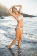 Beautiful smiling blonde in white bikini at the beach with wet h