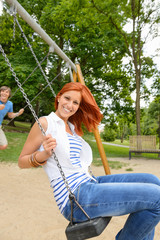 Two teenagers sitting swing in park playground