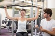 Fit brunette using weights machine for arms with trainer taking