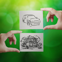 hand holding hand drawn house and car on canvas board on nature