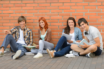 College students sitting ground by brick wall