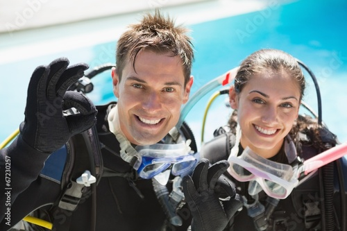 Smiling couple on scuba training in swimming pool showing ok ges