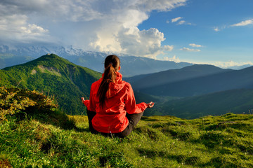 Young woman in red jacket sitting in yoga pose in mountains