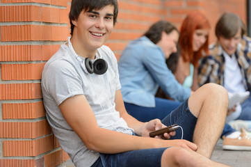 College student boy sitting ground with friends