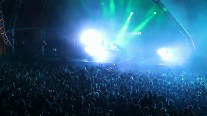 Huge crowd dancing at a DJ show, with great lightning effects