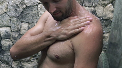 Man washing his body under shower, super slow motion