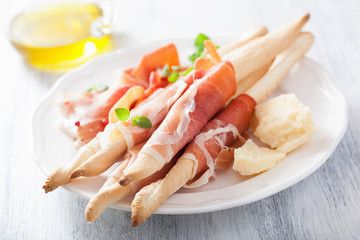 prosciutto ham and grissini bread sticks. italian antipasto