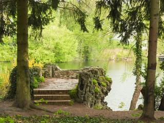 Resting place at a lake surrounded by fresh green trees