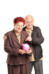 Senior couple putting money into a piggybank