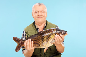 Mature male fisherman holding a freshwater fish