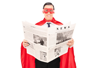 Masked superhero reading the news