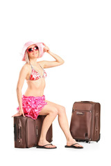Beautiful female tourist sitting on her luggage