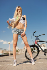young sexy woman with bike outdoors