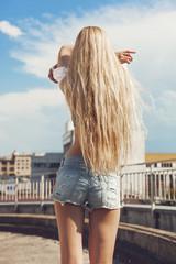 Blonde woman taking off  t-shirt
