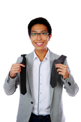 Happy asian man trying to choose a tie over white background