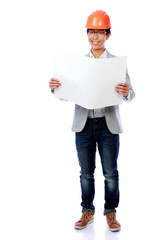 Asian young man wearing a hardhat looking at blueprint paper