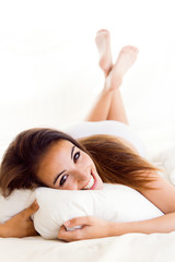Beautiful girl lying on the bed. Isolated on white.
