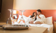 Leinwanddruck Bild - Smiling couple with champagne glasses in bed