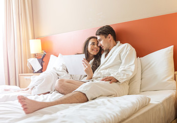 Young Couple lying in the bed of a hotel room