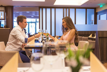 Young Couple toasting in restaurant with wine glasses
