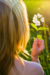 I love nature, blonde woman holding flower