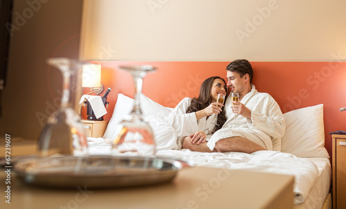 Smiling couple with champagne glasses in bed - 67239607