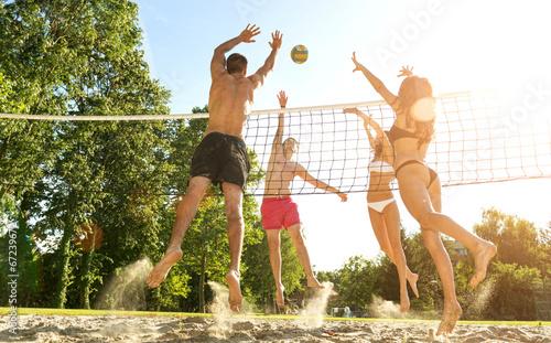 Leinwanddruck Bild Group young  Friends Playing Volleyball On Beach
