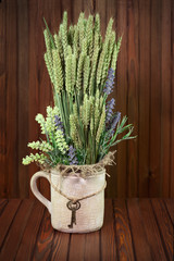 Still life of flowers and ears of rye in vintage vase with keys.