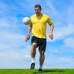 Brazilian soccer football player doing kicky ups on a sky backgr