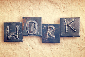 """The word """"WORK"""" made from metal letters on an old vintage paper"""