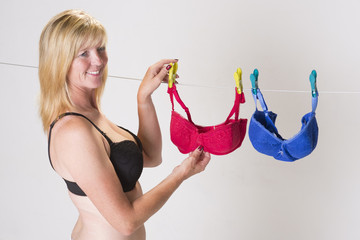 Woman wearing black bra hanging washing on the line