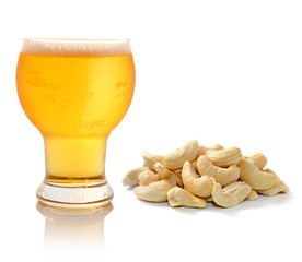 Glass of light beer and cashew nuts  isolated on white