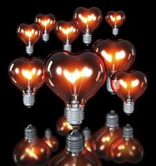 Gruppe Klassische Glühlampe in Herzform, schwarzer Hintergrund