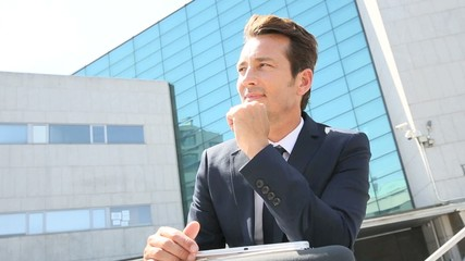 Portrait of businessman sitting outside office building